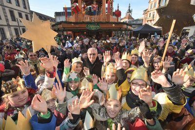 Bischof Heinz Josef Algermissen ist umringt von dutzenden Sternsingern. Er ist glücklich über all die Menschen, Farben und Dynamik die ihn umgibt. Im Hintergrund ist der Weihnachtsmarkt und verschiedene Buden wie ein Glühwein und Kakaostand zu sehen.