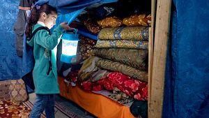Hinter einem Vorhang im Zelt hat die Familie bunte Matratzen verstaut, die sie nachts zum Schlafen auf dem Boden auslegen.