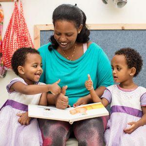 Auf dem Bild ist ein Zwillingspaar zusammen mit einer Betreuerin zu sehen. Sie sitzen auf dem Boden und Lesen ein Bilderbuch. Alle Lächeln halten die Hand vor den Körper und strecken den den Daumen in die Luft.