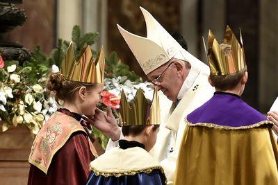 Drei Sternsinger stehen vor Papst Franziskus. Sie haben die traditionellen Gewänder an. Die Sternsinger haben an der Gabenprozession teilgenommen. Papst Franziskus Blick gütig auf die Sternsinger und berührt einen von ihnen an der Wange und lächelt.
