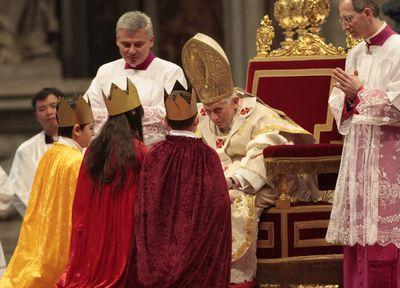 Drei Sternsinger stehen vor Papst Benedikt. Sie haben die traditionellen Gewänder an. Die Sternsinger knien vor dem Papst der in seinem Thron sitzt. Papst Benedikt hat sich in seinem Thron nach vorne gebeugt um besser mit den Sternsingern reden zu können.