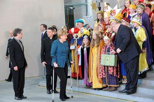 Bundeskanzlerin zusammen mit den Sternsinger die sch auf einer großen Treppe aufgestellt haben. Peter Altmeter übergibt einen kleinen Koffern eine Sternsingerin und Prälat Krämer geht hinter Angela Merkel her.