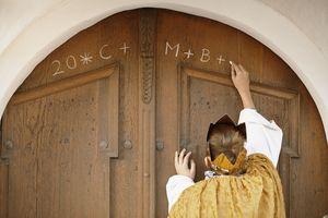 Ein Sternsinger schreibt den traditionellen Segen der Sternsinger an eine Haustür.