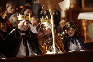 Sternsinger beim Gottesdienst. Sie haben Kronen und Umhänge sowie den Stern dabei. Sie sitzen in der ersten Reihe der Kirche.