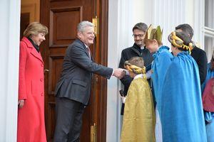 Bundespräsident Joachim Gauck und seine Frau begrüßen die Sternsinger im Schloss Bellevue. Die Sternsinger tragen bunte Umhänge und haben goldenen Kronen an. Der Bundespräsident Joachim Gauck reicht einem der Sternsinger die Hand und begrüßt ihn.