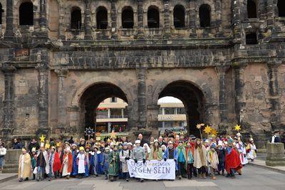 Treffpunkt Porta Nigra: 2.659 Sternsinger feiern am Freitag, 29. Dezember, in Trier die bundesweite Eröffnung ihrer 60. Aktion Dreikönigssingen. Hier laufen die Sternsinger grade durch das Porta Nigra in Trier und tragen das Banner mit dem Slogan der Sternsinger voran. Der Slogan lautet Segen bringen, Segen sein.
