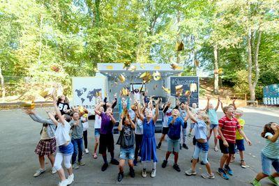 Viele Kinder springen hoch und werfen goldene Papierkronen in die Luft. Im Hintergrund ist ein ein weißer Transporter zu sehen, der ausgeklappt ist.