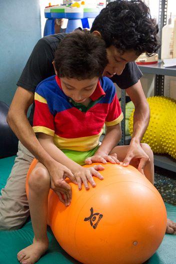 Ein Physiotherapeut hilf einem körperlich beeinträchtigtem Jungen bei der Bewegung.
