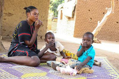 Im Schatten eines Mangobaums isst die Familie draußen auf einer geflochtenen Matte.