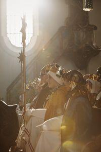 Sternsinger setzten in der ersten Reihe in der Kirche. Sie haben Gewänder und Kronen an. Im Hintergrund kann man noch das Inventar und die Verzierungen der Kirche erkennen.
