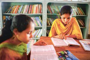 Zwei Mädchen in traditioneller indischer Kleidung sitzen an einem Tisch und lesen Bücher. Im Hintergrund sind Regale die voll mit Büchern sind. Die Mädchen sind konzentriert und lernen für die Schule.
