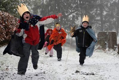 Dieser vierköpfige Sternsingergruppe läuft einen verschneiten Weg entlang. Sie tragen bunte Umhänge und goldene Kronen. Die Sternsinger sind voller Energie und freuen sich darüber, dass sie unterwegs sind.