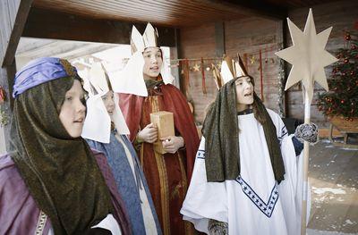 Drei Sternsinger stehen vor einer Haustür und singen. Sie tragen die Gewänder der Heiligen Drei Könige, die Kronen, den Stern von Betlehem und Singen.
