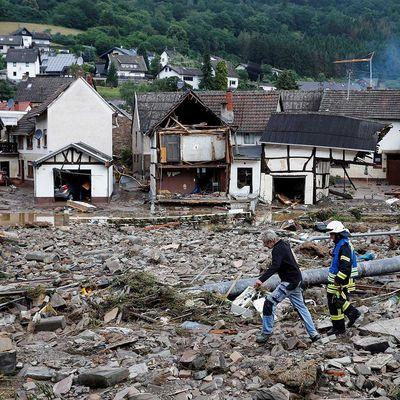 Ein Mann und ein Feuerwehrmann gehen nach heftigen Regenfällen im Ort Schuld am 15. Juli 2021 durch Trümmer.