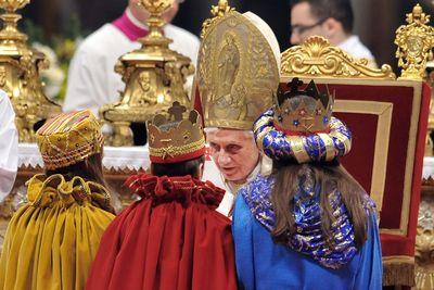Drei Sternsinger empfangen den Segen von Papst Benedikt. Die Sternsinger haben ihre bunten Umhänge an und tragen goldene Kronen auf dm Kopf. Der Papst hat sich in seinem Stuhl etwas nach vorne gebeugt um besser mit den Sternsinger reden zu können. Papst Benedikt trägt sein volles Ornat.