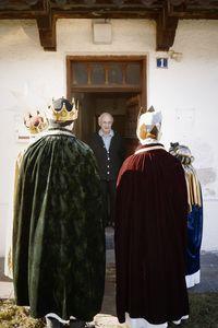 Ein älterer Mann freut sich über den Besuch der Sternsinger bei ihm zuhause.
