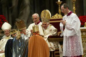 Drei Sternsinger knien vor dem Papst. Sie haben die traditionellen Gewänder an und tragen die goldenen Kronen auf dem Kopf. Der Papst segnet die Sternsinger. Um das besser tun zu können hat er sich in seinem Stuhl weiter nach vorne gebeugt.