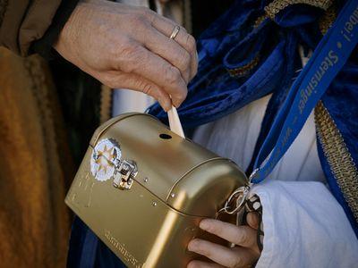 Ein Sternsinger hält die goldene Spendenbox in den Händen. Eine andere Person wirft gerade eine Spende in diese Box. Die Box ist mit einem Sternsingeraufkleber versiegelt.