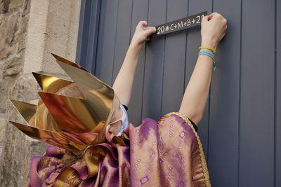 Ein Sternsinger klebt mit Mund-Nasen-Bedeckung den neuen Sternsingersegen an eine Haustür.