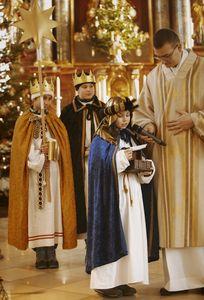 Drei Sternsinger sind Teil des Gottesdienstes. Ein Sternsinger bekommt das Mikrofon durch den Priester herangereicht und spricht.