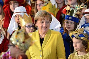 Bundeskanzlerin inmitten vieler Sternsinger die zu Besuch im Bundeskanzleramt sind.
