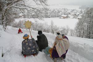 Mit dem Schlitten geht es für diese Sternsinger zum nächsten Haus. Über tiefverschneite Felder sausen sie ins nächste Dorf um auch dort den Menschen dennSegen zu bringen.