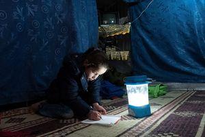 Konzentriert sitzt Nour auf dem Zeltboden und zeichnet mit dem Bleistift ein Gesicht auf ein Blatt Papier.