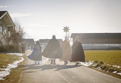 Vier Sternsinger auf dem Weg zu einem Gehöft. Sie gehen in strahlendem Sonnenschein einen Schotterweg entlang. Alle gehen nebeneinander und den Stern haben sie in der Mitte.