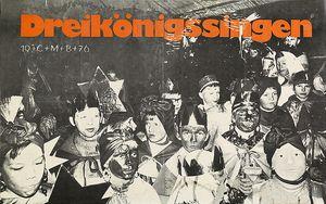 Ein Plakat der Sternsinger aus dem Jahr 1976. Das Plakat ist schwarz und weiß. Das Motiv ist ein schwarz- weiß Foto von achtzehn Sternsingern. Die Sternsinger haben Gewänder und Kronen an. In der Kopfzeile des Plakats steht in orangener Farbe Dreikönigssingen.