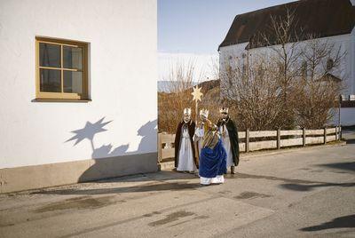 Vier Sternsinger auf dem Weg von der Kirche zu den Menschen nach Hause. Sie sind in die traditionellen Gewänder gehüllt, tragen Kronen und den Stern von Betlehem.