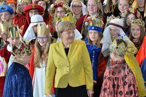 Bundeskanzlerin Angela Merkel inmitten vieler Sternsinger die zum Besuch im Bundeskanzleramt sind.