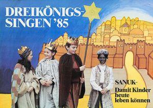 Ein Plakat zur Aktion Dreikönigssingen aus dem Jahr 1985. Abgebildet ist eine vierköpfige Sternsingergruppe. Die Sternsinger tragen die traditionellen Gewänder der Heiligen Drei Könige. Ausserdem tragen sie Kronen und haben an einen Stock den Stern von Bethlehem befestigt. Der Hintergrund ist eine Zeichnung der Stadt Jerusalem. Die Stadt ist von Hohen Mauern umgeben und die Häuser ragen wie Berge in die Höhe. Die Stadt ist Hell erleuchtet und strahlt ihr licht hinaus in die dunkle Nacht.