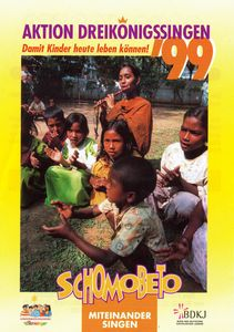 Ein Aktionsplakat zur Aktion Dreikönigssingen 1999. Das Aktionsland ist Bangladesch. Abgebildet sind sieben Kinder und eine Lehrerin. Die Mädchen und Jungen singen und klatschen während die Lehrerin begleitend auf einer traditionellen Flöte aus Bangladesch spielt. Die gesamte Szene spielt sich draußen im Grünen ab. Alle hocken zusammen auf dem Boden. In derKopfzeile steht Aktion Dreikönigssingen ´99. Direkt darunter der Spruch: Damit Kinder heute leben können. In der Fußzeile steht Schombeto, das Wort bedeutet miteinander Singen.