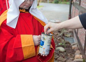 Ein Sternsinger in traditioneller Kleidung hält die Spendendose vor sich. Eine Person wirft etwas Geld als Spende hinein.