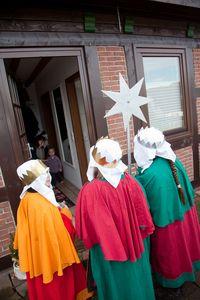 Drei Sternsinger stehen an der Tür einer Hütte und geben ein Sternsingerlied zum Besten. Die Sternsinger haben die traditionellen Gewänder der Heiligen Drei Könige an.