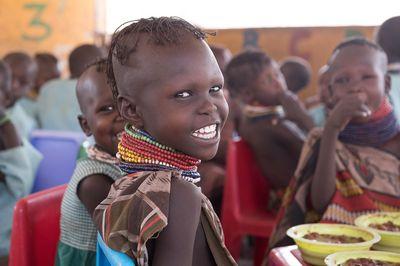 Aweet sitzt am Tisch mit anderen Kindern. Sie ist in einem Gesundheitszentrum, lächelt und hat essen vor sich auf dem Tisch stehen.