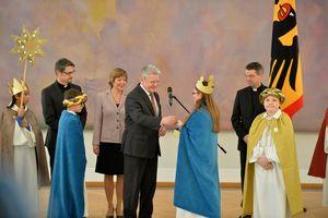 Bundespräsident Joachim Gauck übergibt einer Sternsingerin eine Spende. Die Sternsingern hält die Spendenbox vor sich und Joachim Gauck wirft seine Spende in die Spendenbox. Im Hintergrund stehen seine Frau Daniela Schadt und Prälat Dr. Klaus Krämer