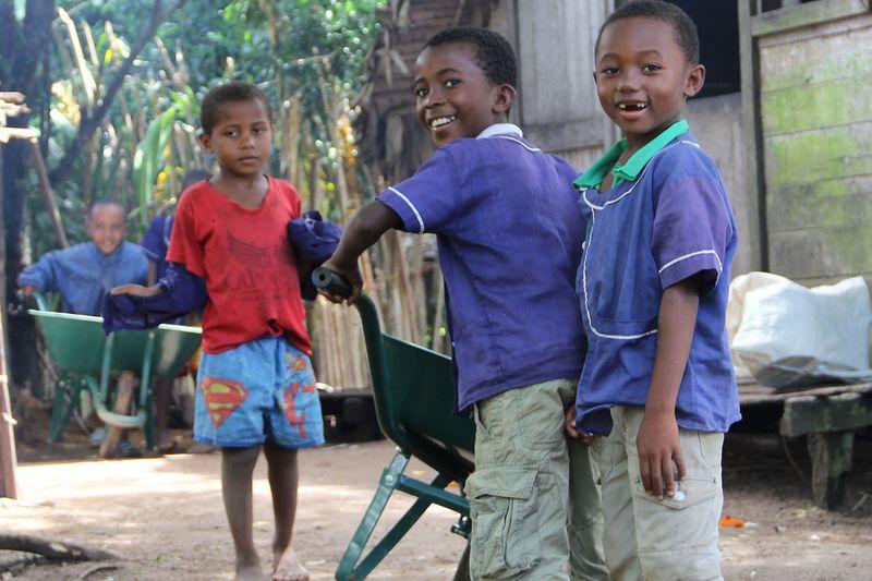 """Ob sägen, gießen oder neue Erde mit der Schubkarre transportieren – in der """"Grünen Schule"""" helfen alle bei der Gartenarbeit und haben viel Spaß dabei. Wie diese beiden Jungen beim schieben einer Schubkarre."""