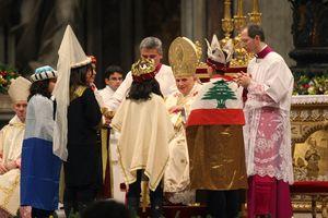 Vier Sternsinger sind vorne beim Papst und unterhalten sich mit Ihm. Die Sternsinger haben die Gewänder und Kronen der Heiligen Drei Könige an. Einer der Sternsinger hat die Nationalflagge des Libanon auf den Rücken. Die Flagge ist rot und weiß und hat und er Mitte eine grüne Tanne.