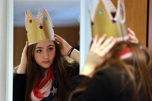 Jana probiert ihre neue Krone vor einem Spiegel an und betrachtet die Verzierungen.