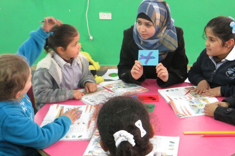 Vier Kinder beim Unterricht mit einer Lehrerin.