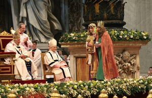 Drei Sternsinger nehmen an der Gabenprozession im Petersdom teil und bringen die Gaben zum Papst. Die Sternsinger haben die Gewänder und Kronen an. Der Papst sitzt auf seinem Thron und blickt den Sternsingern entgegen. Die Sternsinger bringen Gaben mit. Sie haben eine Spendendose, Weihrauch und einen goldenen Gral dabei.