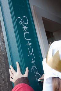 Ein Sternsinger mit Krone und Gewand schreibt den traditionellen Segen der Sternsinger an den Türrahmen einer Haustür.