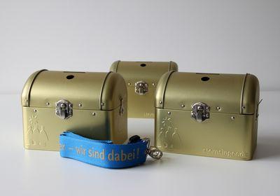 Drei Spendendosen stehen auf dem Tisch. Die Dosen sind golden und verschlossen. In die Vorderseiten der Dosen ist das Logo und der Schriftzug der Sternsinger eingestanzt. Das Band indem die Dose schließlich um den Hals getragen werden kann ist blau und druckt. Das Band liegt auch auf dem Tisch.