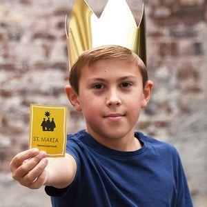 Ein Junge mit Krone hält ein Sternsinger-Logo in die Kamera