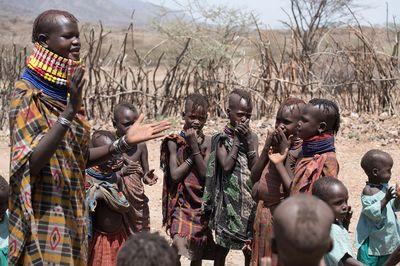 Viele Kinder stehen um eine Frau herum, sie klatschen in die Hände und bekommen etwas beigebracht.