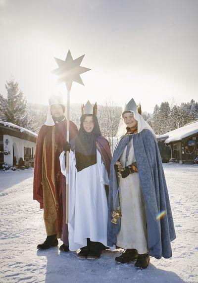 Diese dreiköpfige Gruppe der Sternsinger ist gekleidet in lange Umhänge und glitzernde Kronen. Sie tragen lila farbene, blaue und rote Umhänge. Die Gruppe steht im Schnee und die Sonne steht schon tief am Himmel. Der Stern der Sternsinger strahlt weil die Lichtstrahlen den Stern von hinten erleuchten.
