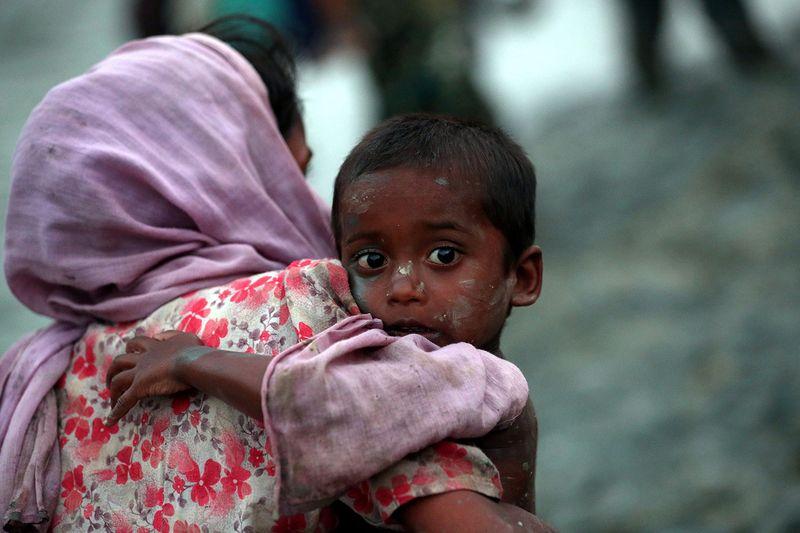 Eine Rohingya trägt ihr Kind über die Grenze.