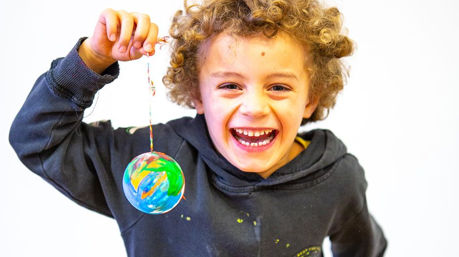 Junge mit selbst gestalteter Christbaumkugel