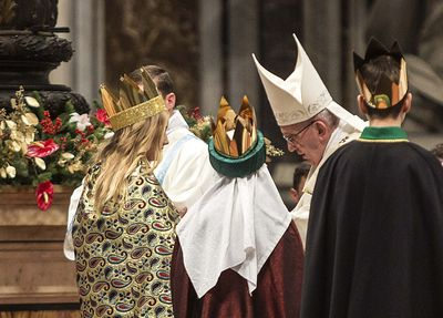 Drei Sternsinger stehen vor Papst Franziskus. Sie haben die traditionellen Gewänder an. Die Sternsinger haben an der Gabenprozession teilgenommen. Die drei stehen direkt vor dem Papst.